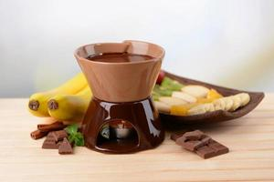 Chocolate fondue with fruits on light background