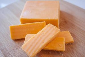 bloque de queso cheddar y rodajas foto