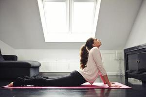 Woman doing stretching on mat at home
