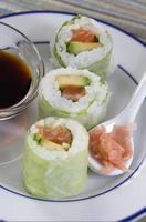 Delicious sushi rolls on white plate with