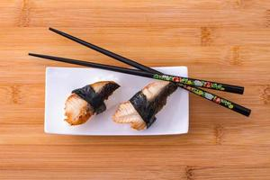 Two nigiri eel sushi with chopstick on bamboo board
