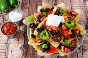 Fully loaded Mexican nacho chips on rustic wood background
