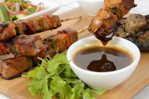 Barbecue glazed pork kebabs on wood board photo