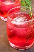 Glasses of refreshment raspberry flavour fizz with ice and rosemary