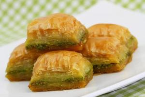 Pistachio baklava stocked up on white plate, closeup