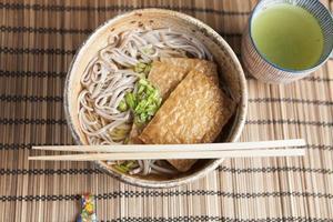 Kitsune soba, Japanese buckwheat noodles with marinated, fried tofu photo