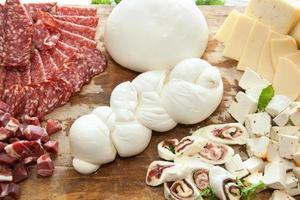 trenza en forma de mozzarella en tabla de cortar con salami y queso foto