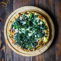 Spinach and goat cheese pizza on wooden background