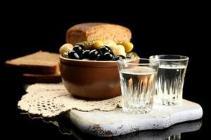 Composition with glasses  of vodka, and food isolated on black photo