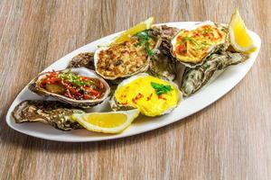 White dish with baked oyster shell cheese, salad oysters, served photo