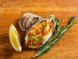 Baked oyster shell with cheese, served greens and lemon photo