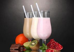 Milk shakes with fruits and chocolate on grey background