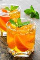 Cold drinks with ice and mint. Orange cocktail on rustic