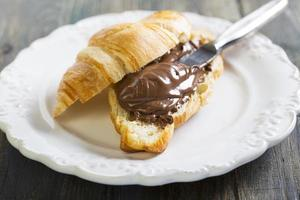Plate with croissant and chocolate.
