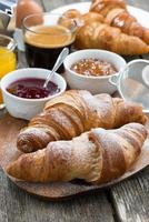 delicious breakfast with fresh croissants, vertical photo