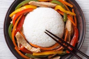 Asian rice with chicken and vegetables closeup top view photo