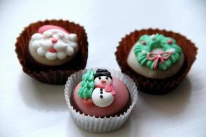 três sobremesas de chocolate de Natal em uma bancada da cozinha.