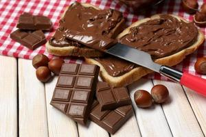 Bread with sweet chocolate hazelnut spread on wooden background photo