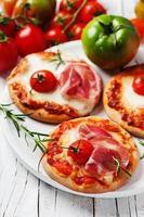 Mini pizza with mozzarella, prosciutto and tomato photo