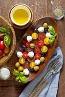 Salad with colored tomatoes, small mozzarella, green olivesand b
