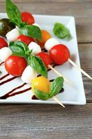 Caprese salad on wooden sticks photo