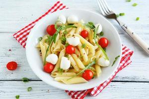 Penne with slices of cheese and tomatoes photo