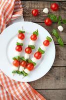 Seasonal traditional Italian caprese salad skewers with tomatoes basil and