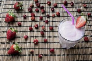 batido de fresa con fresas en el fondo foto