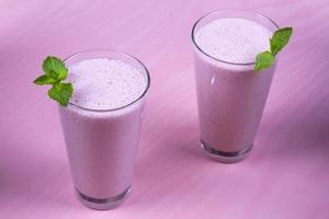 Raspberries milkshake garnished with mint on pink wooden background