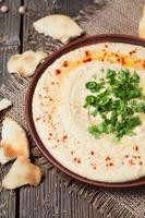 Creamy hummus in clay rustic plate served with pita, paprika