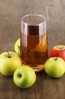 Useful apple juice with apples around on wooden table photo