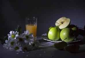 Stillleben mit Gänseblümchen und Äpfeln.