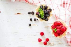 Berry in waffle cones, white wood background