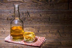 botella con un vaso con whisky en la servilleta foto