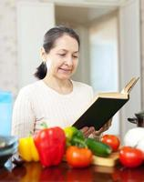 woman reads cookbook for recipe in kitchen
