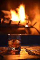 glass of hard liquor with ice cubes and fireplace photo