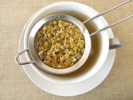 Chamomile flowers tea in tea strainer