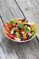 Ensalada de frutas y bayas en mesa de madera, vertical foto