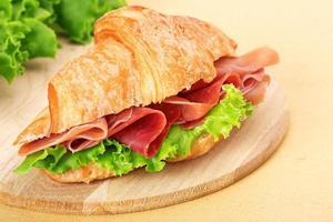 croissant with parma ham and lettuce on chopping board photo
