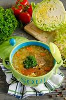 Shchi - traditional russian cabbage soup on a wooden table photo