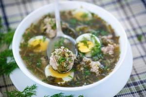 sorrel soup with meatballs and eggs photo