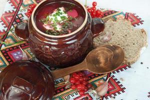 Jabón ucraniano con ajo y pan en la mesa de madera. foto