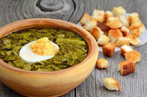 Sorrel soup with egg in wooden bowl