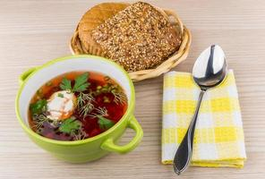Ukrainian borsch, bread in basket, spoon on napkin on table