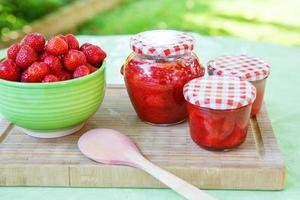 Homemade strawberry jam in different jars and fresh ripe strawbe
