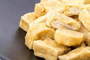 Tofu - deep fried on black dish photo