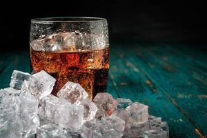 Vaso de cola con hielo en una mesa de madera.