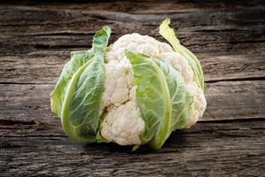 Fresh organic cauliflower on wooden background photo