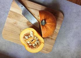 Pumpkin cut in half on wooden cutting board