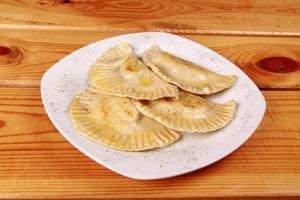 raviolli cocido en un plato blanco brillante foto